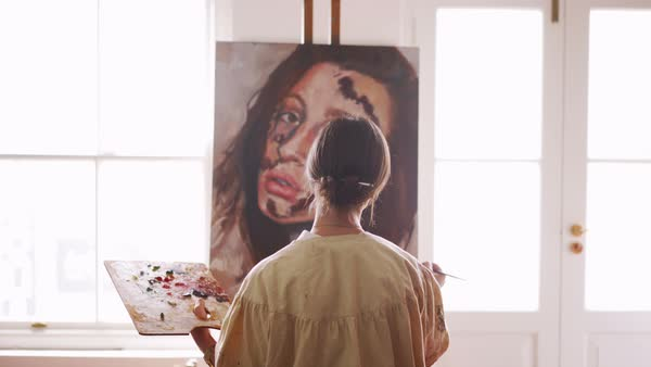 Vintage style rearview shot of a young woman artist mixing paint on a wooden palette while working on a canvas that is resting on an easel placed between the windows of her studio Royalty-free stock video
