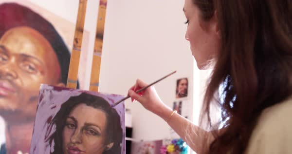 Woman fine artist working on an oil painting resting on an easel in her beautifully lit studio while wearing an old-fashioned traditional artist's smock Royalty-free stock video