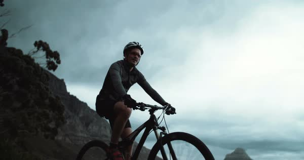 Upward shot of determined cyclist in recreational pursuit for competitive sport with bicycle on mountain side road just after sundown with mountain silhouettes in the background Royalty-free stock video