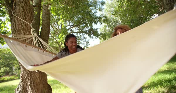 Engaging family spends a relaxing day outdoors together in the shade of a tree hanging on a hammock Royalty-free stock video