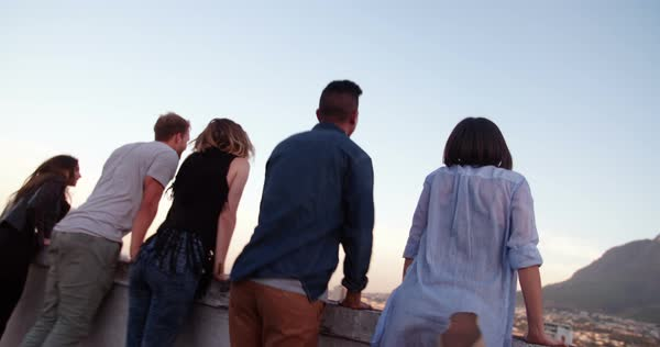 Happy teenager friends embracing and laughing while watching the sunset over the city leaning on the parapet of a rooftop Royalty-free stock video