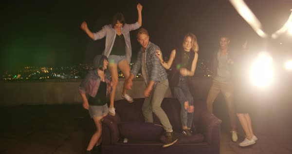 Group of teenager friends dancing with raised arms and laughing during a night rooftop party Royalty-free stock video