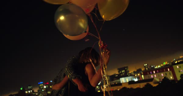 Happy teenager couple celebrating by holding some colourful ballons on the rooftoop while hugging and looking at citylights Royalty-free stock video