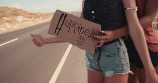 Hipster woman and hipster woman in the daytime stand on side of two lane highway hitchhiking while holding cardboard sign with the word Happiness written on it and sticking out thumb Royalty-free stock video