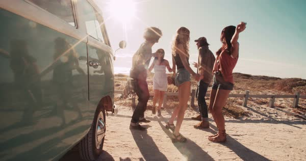 A group of hipster road trip friends laughing and talking while dancing next to a parked retro van next to a sandy beach during sunset Royalty-free stock video