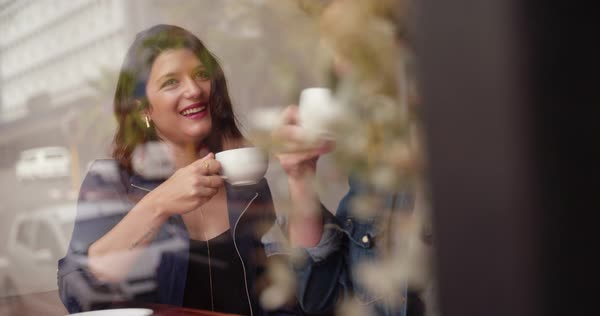A window shot of a man and a woman sipping their coffee in a coffee shop in the daytime with the reflection of city outside on window Royalty-free stock video