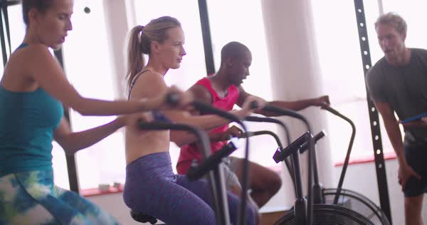 Group of friends doing an indoor cycling workout during a crossfit training class headed by a personal trainer with a modern digital tablet Royalty-free stock video