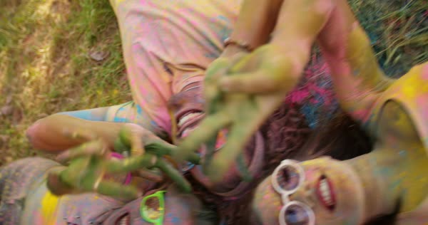 Group of young women standing together making silly faces and gesturing peace sign with hands while covered in Holi powder Royalty-free stock video