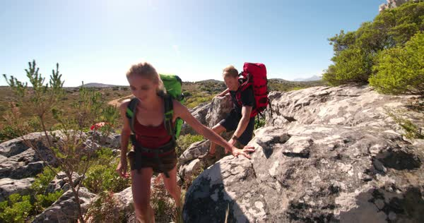 Couple hiking together with backpacks in rocky landscape exploring nature and adventures Royalty-free stock video