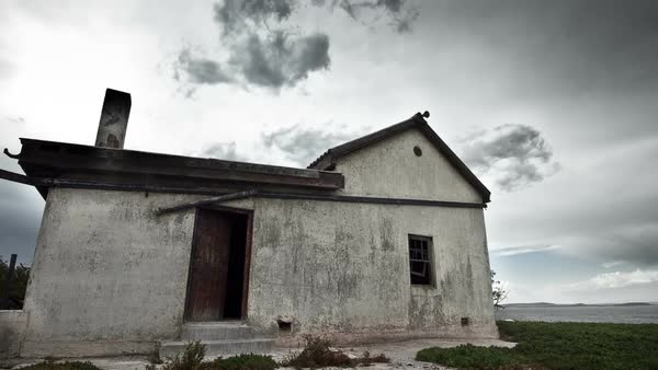 Timelapse of grey sky clouds passing over abandoned decaying house by the sea Royalty-free stock video