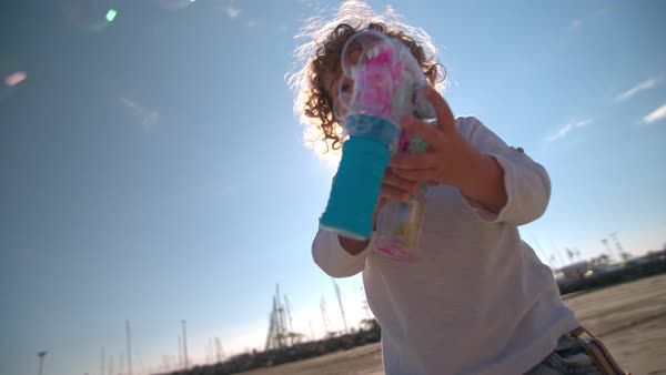 Cute young boy blowing bubbles, smiling and excitedly trying to catch them Royalty-free stock video