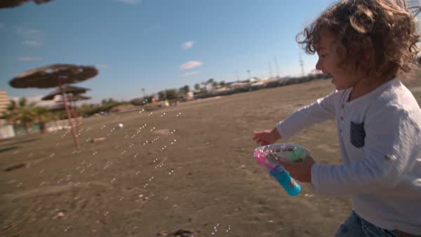 Adorable curly boy having fun at the beach, blowing bubbles in the wind and running Royalty-free stock video