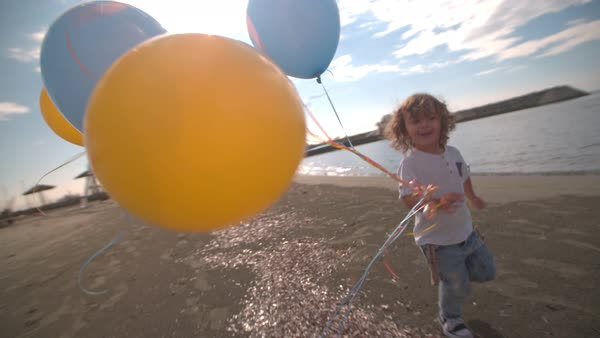 Cute curly boy running at the seashore, holding balloons and smiling Royalty-free stock video