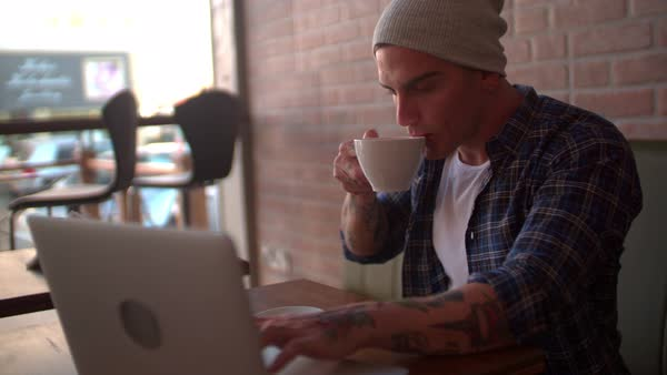 Cool young hipster drinking cappuccino, searching online on his computer in hip coffee shop Royalty-free stock video