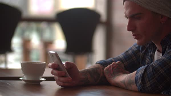 Handsome young man browsing online on his touch-screen smartphone while having coffee alone and waiting at cafeteria Royalty-free stock video