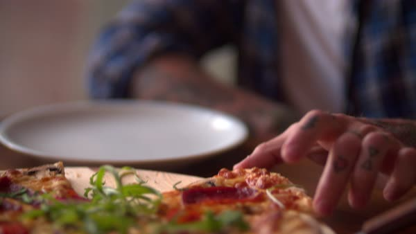 Close up of young hipster with tattoos in casual wear taking a slice of pizza and biting it Royalty-free stock video