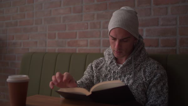 Attractive young college student reading a book and flipping a page while having coffee in modern cafe Royalty-free stock video