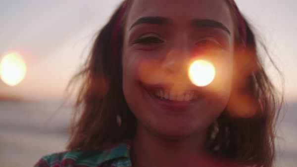 Happy brunette young woman holding fireworks and smiling at the beach at sunset Royalty-free stock video