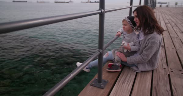 Mother and little son sitting together on pier looking at the ships in the sea Royalty-free stock video