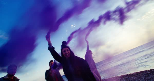 Group of young friends celebrating, running and holding smoke bombs next to the sea Royalty-free stock video