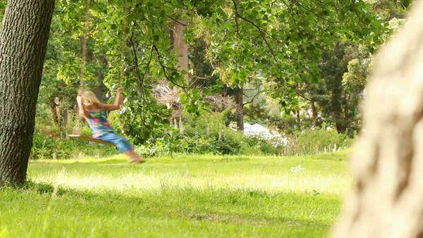 Little girl is having big fun on the swing in the park/garden Royalty-free stock video