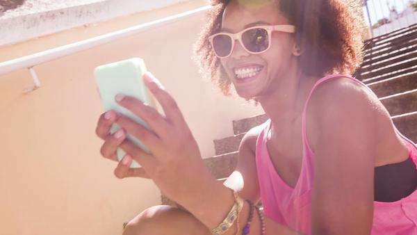 Afro haired girl texting on smartphone Royalty-free stock video