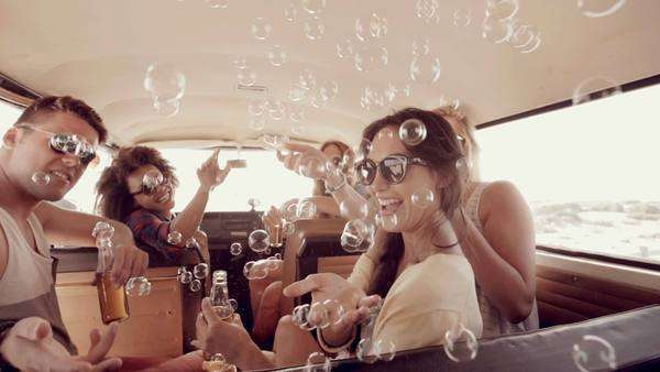 Hipsters blowing bubbles in camper van Royalty-free stock video