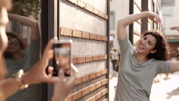 Young woman uses smartphone to take photo of friend waving in street Royalty-free stock video