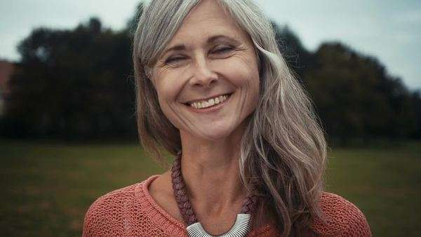 Close-up of radiant mature woman smiles whilst standing in park Royalty-free stock video
