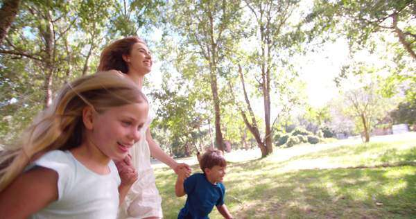 Young mom and her children having fun running slow motion freely in a sunny park Royalty-free stock video