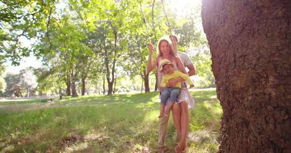 Happy dad pushing mom and their little girl on a swing under a tree in slow motion Royalty-free stock video