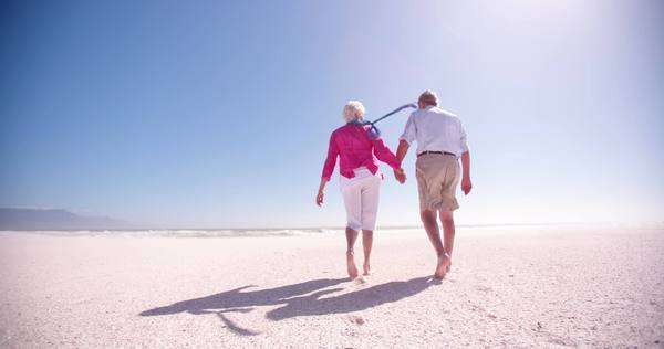 Rear view of an elderly retired couple walking together along the beach in slow motion Royalty-free stock video