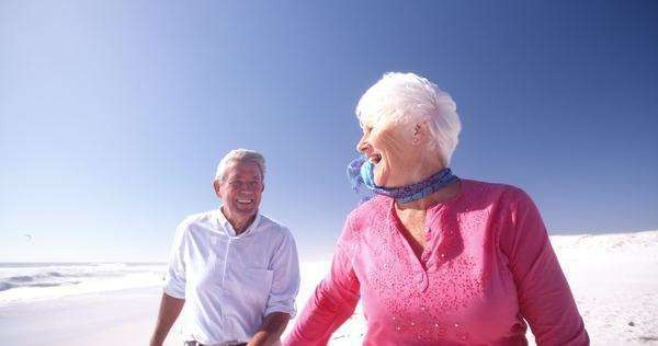 Smiling senior adult woman walking with her husband on the beach holding hands in slow motion Royalty-free stock video