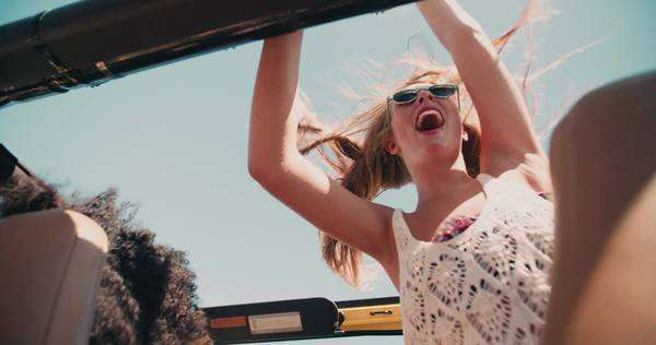 Blonde teenage girl standing and waving happily in an open top vehicle on a road trip in slow motion Royalty-free stock video