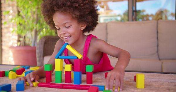 Smiling little Afro girl playing happily in her home with colorful building blocks Royalty-free stock video
