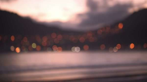 Out of focus seaside and city at sunset Royalty-free stock video