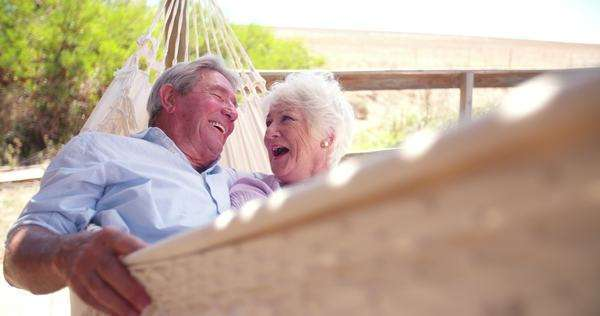 slow motion video of a loving retired senior couple swinging in hammock and laughing together Royalty-free stock video