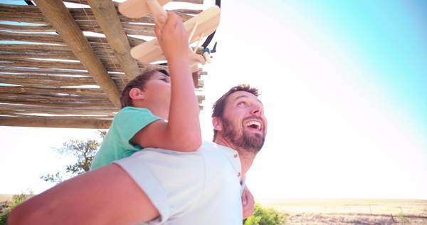 Smiling father piggybacking his little son who is playing with a toy plane made of wood Royalty-free stock video