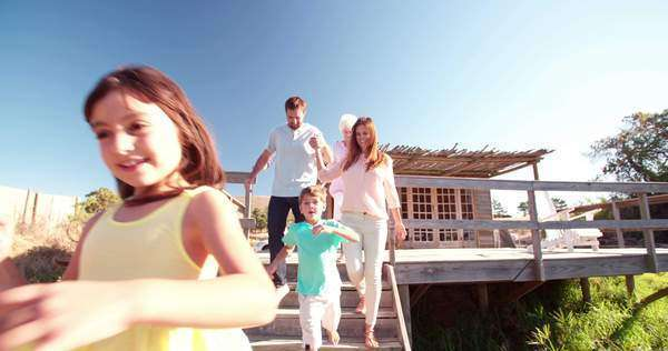 Loving couple holding hands while their children run happily on a jetty, followed by the grandparents, panning in slow motion Royalty-free stock video