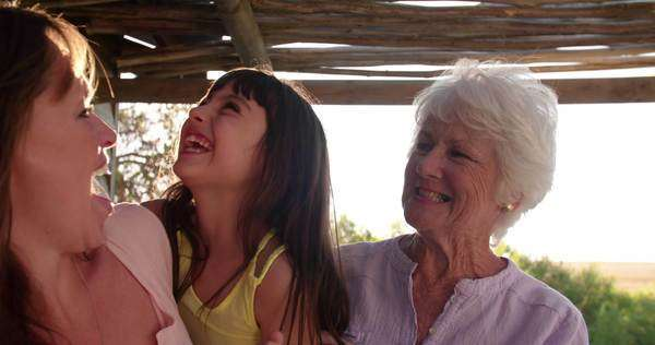 Happy little girl outside with her mother and grandmother smiling together in slow motion Royalty-free stock video