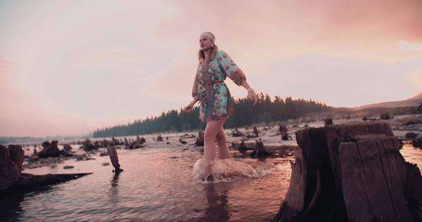 Boho girl with cloudy sky behind her walking through a shallow lake at sunset Royalty-free stock video