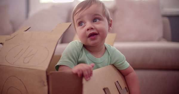 Baby boy at home playing in an old cardboard box in the living room in slow motion Royalty-free stock video