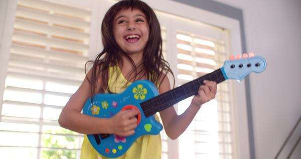 Laughing little girl playing her guitar on the couch in the lounge in slow motion Royalty-free stock video