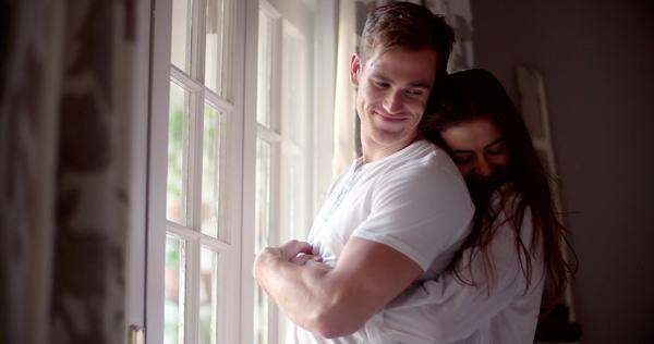 Young couple hugging next to the window in the morning in their bedroom in slow motion Royalty-free stock video