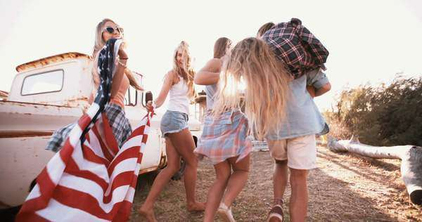 Full length shot of a group of American teens walking together with a flag over their shoulders into sun flare, panning in slow motion Royalty-free stock video