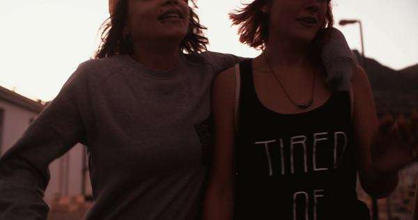 Laughing teen grunge girl friends in an industrial area walking looking at something off to the side, panning in slow motion Royalty-free stock video