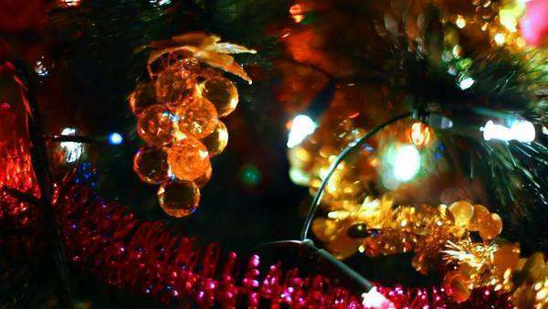 toy in form of glass grapes hanging on Christmas tree among glowing garlands, close-up Royalty-free stock video