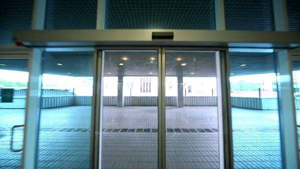 Man Walks Through Entrance Glass Door Of Office Building Stock