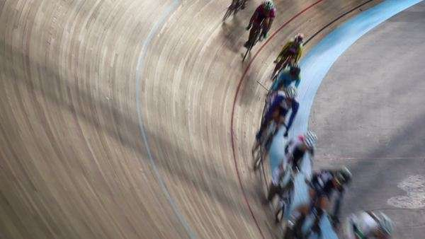 Cyclists ride by track turn during race in stadium Royalty-free stock video