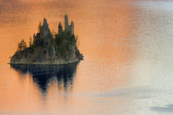 USA, Oregon, Crater Lake National Park. Phantom Ship Island surrounded by golden glimmer at sunrise. Royalty-free stock photo
